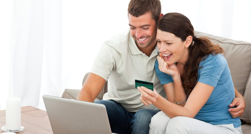 Happy couple looking at their accounts online sitting on the sofa at home
